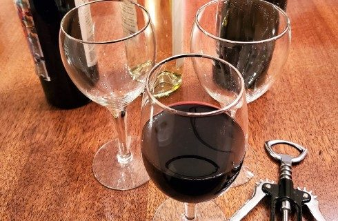 Three wine glasses; one filled with red wine, on a brown table with three bottles of wine and a bottle opener