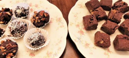 Two round white plates; one holding various chocolate truffles and the other chocolate brownies
