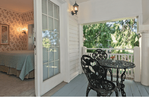 Outdoor covered deck with black table and two chairs and French doors open into a guestroom