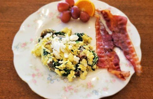 Round white plate with egg scramble two pieces of bacon and grapes