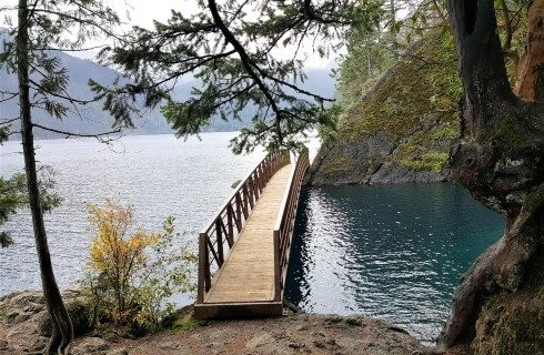 Small bridge over a body of water with trees and a mountain range in the distance
