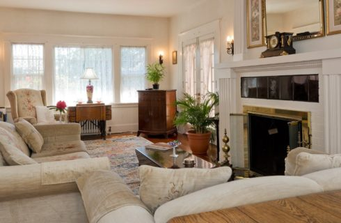 Beautiful white living room with couch and loveseat, fireplace with large mantle, bright windows and French doors