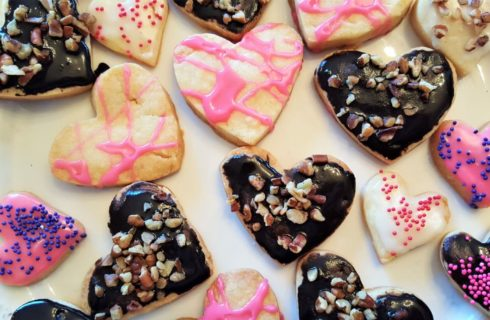 Heart shaped cookies with chocolate and pink frosting and sprinkles on a white platter