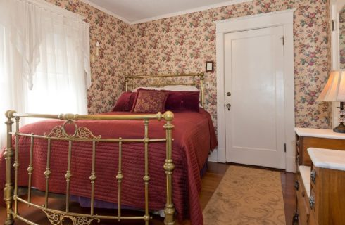 Queen bed with antique brass frame in bedroom with flowered wallpaper and large bright window