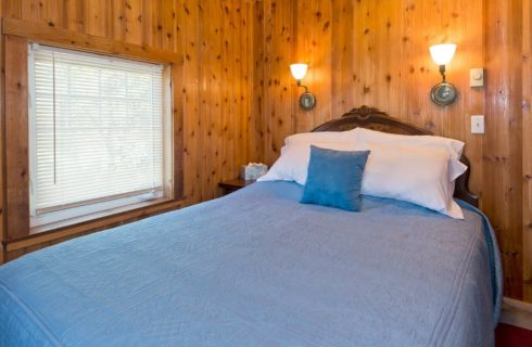 Guest room with wood paneled walls, queen bed with blue quilt and large window