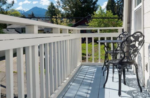 Outside patio with white railings, wrought iron table with two chairs and mountain range in the distance