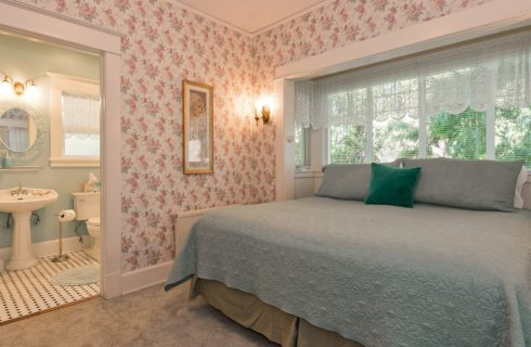 Large bedroom with flower wallpaper, king bed in front of windows and view into bathroom with pedestal sink