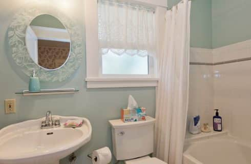 Bathroom with light green walls, pedestal sink, toilet, tiled shower with tub and one window