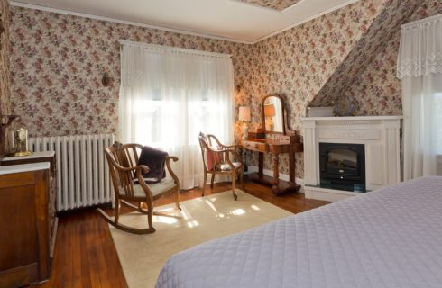 Corner sitting area of a bedroom with two wooden chairs, fireplace, vanity with mirror and large windows