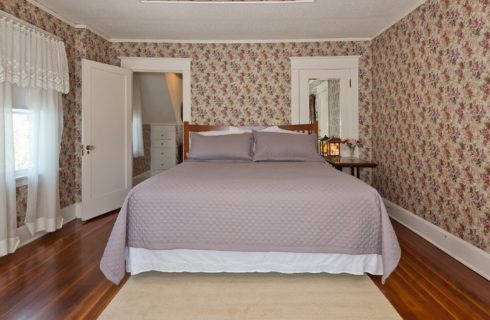 Large guest room with hardwood floors, flowered wallpaper, and king bed with lilac quilt