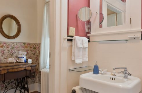 Bathroom with pedestal sink, towel rack and overhead medicine cabinet with doorway into separate room