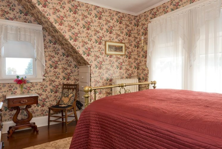 Queen bed with red quilt and brass frame in bedroom with flowered wallpaper and bright windows