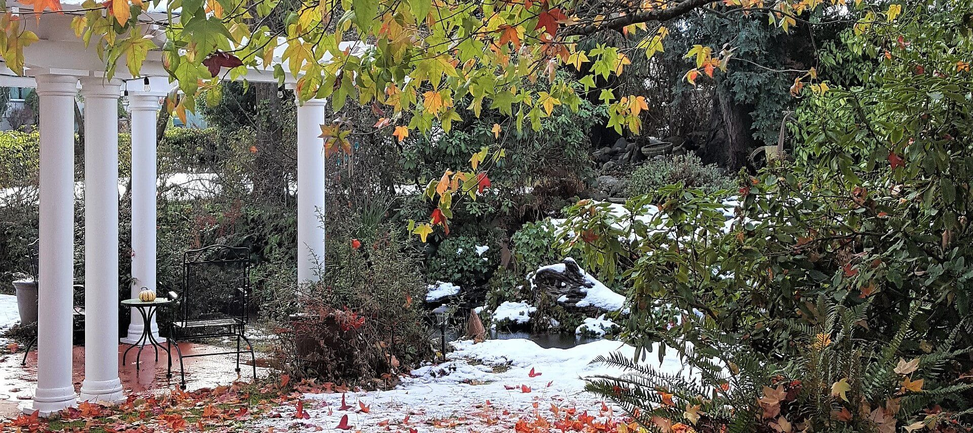 Outside garden with fall leaves and a bit of snow with patio and white pergola with columns
