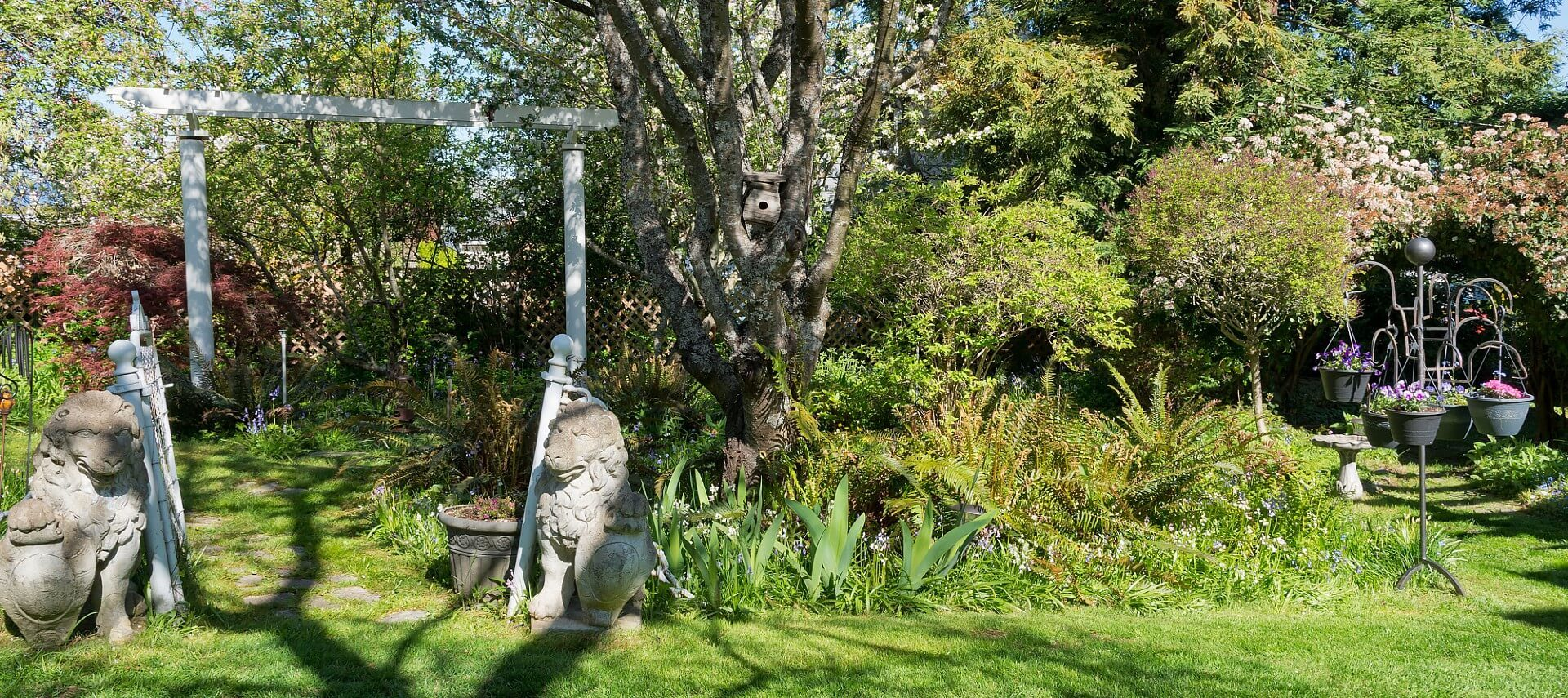 Large garden area with tall white gate by lion statues and stand with hanging baskets