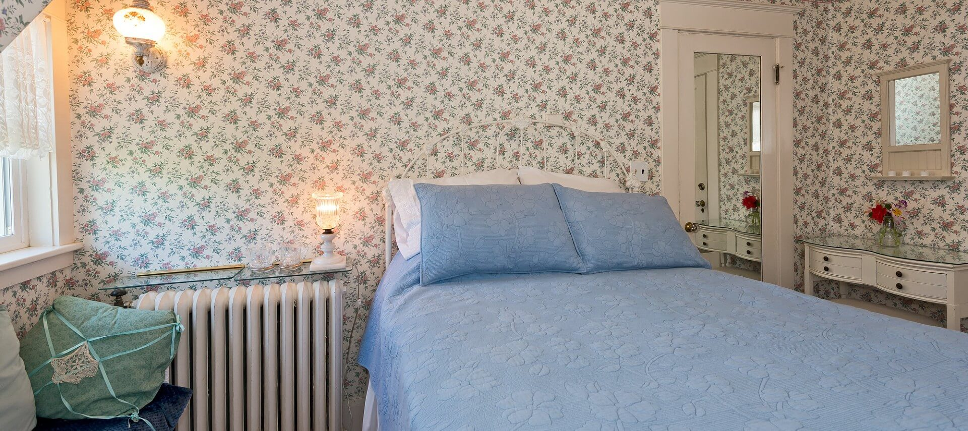 Guest room with flowered wallpaper, bright window and double bed with blue quilt