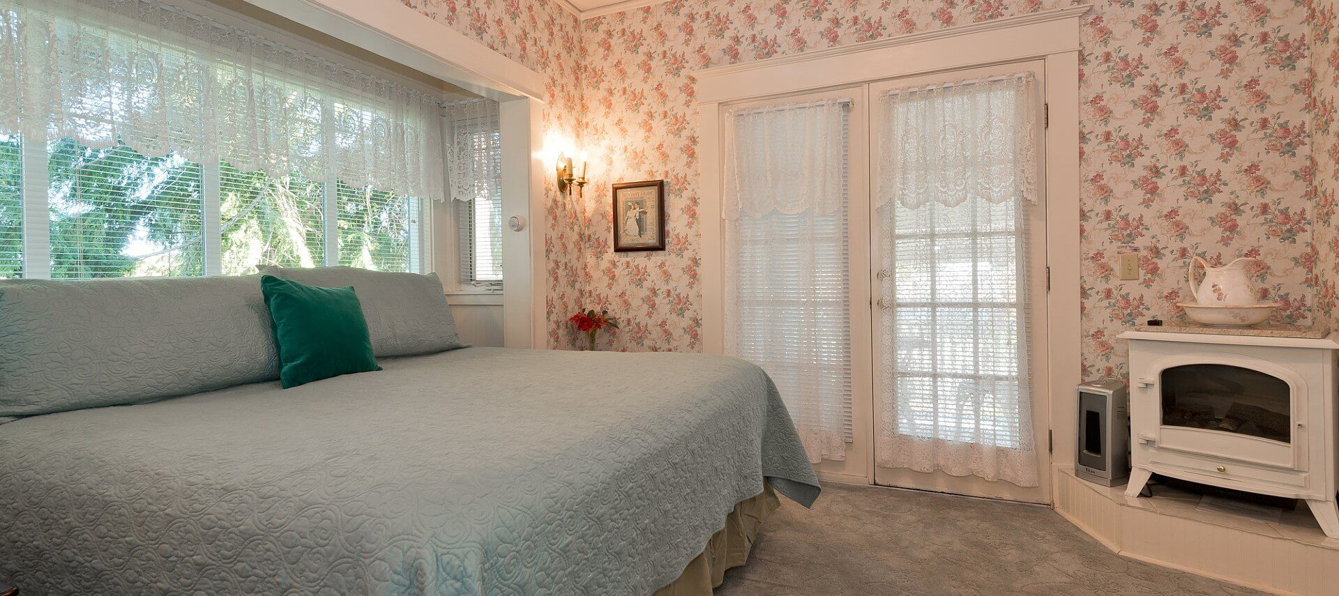 Elegant guest room with king bed, white electric fireplace, bright windows and French doors with lace curtains