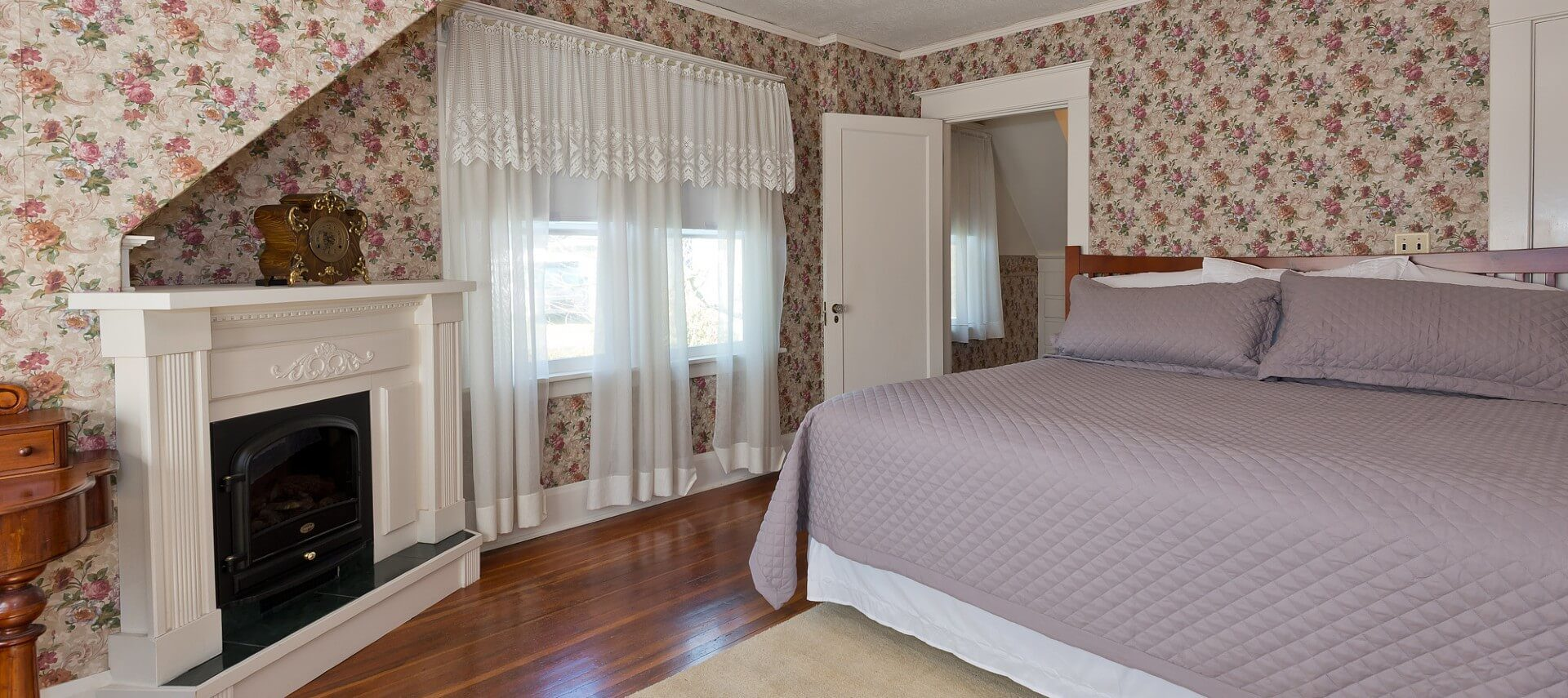 Spacious suite with king bed, fireplace with white mantle, hardwood floors and bright windows