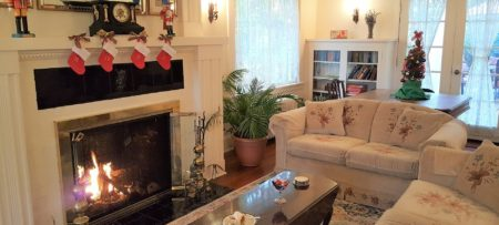 Cozy living room with two couches and coffee table in front of a lit fireplace with mantle holding small stockings