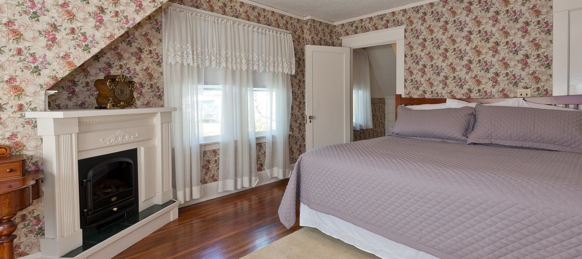 Large guest room with hardwood floors, wallpapered walls, fireplace and king bed with lilac quilt